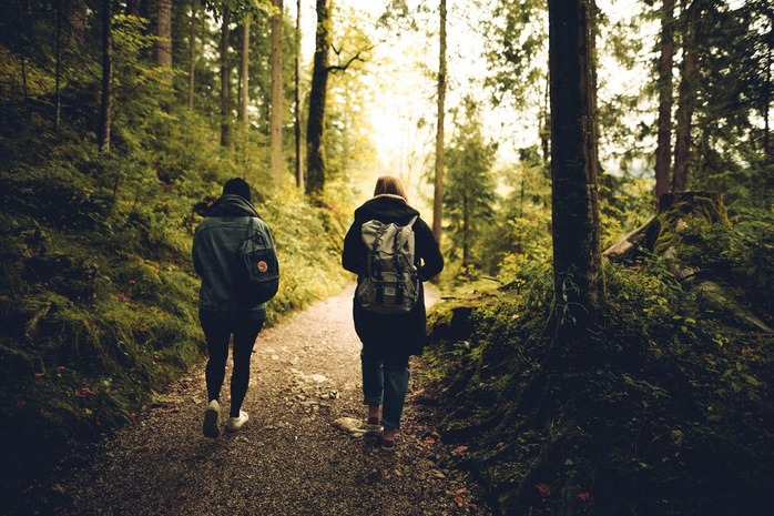 2 people walking on a trail
