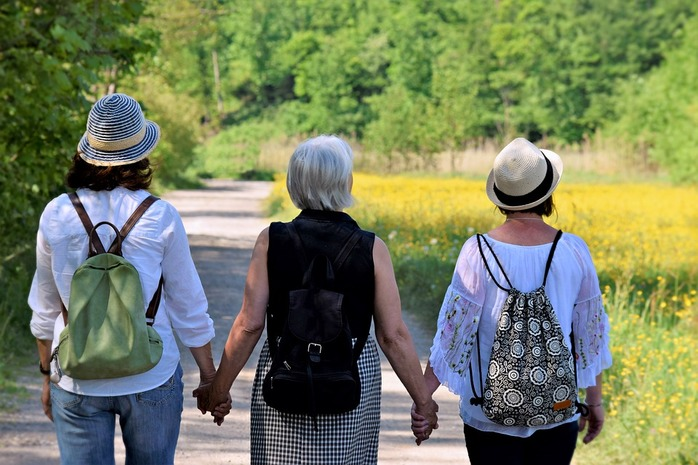 3 women walking and holding hands