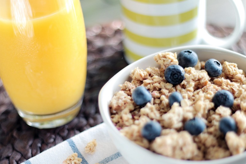bowl of cereal, glass of orange juice, coffee cup