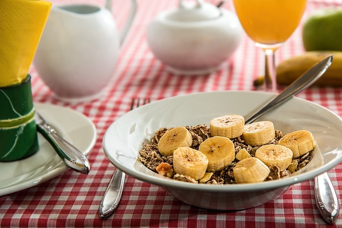 breakfast table with bowl of cereal and orange juice