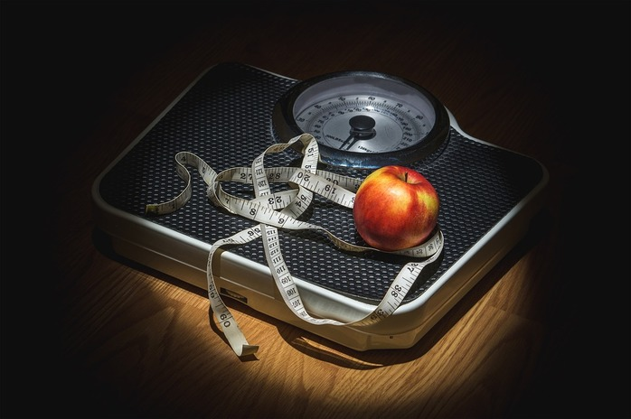 dark background, scale, apple, and measuring tape
