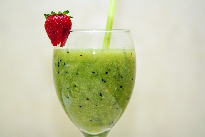 glass of green smoothie and strawberry