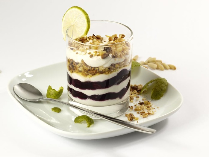 glass of yogurt dessert with chocolate, nuts and a slice of lime