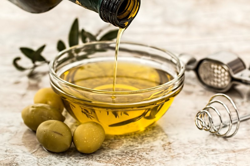 olive oil being poured into a glass container  - Health Benefits of Olive Oil