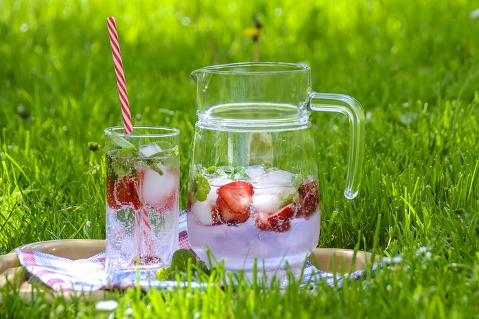 pitcher and glass filled with infused water and strawberries
