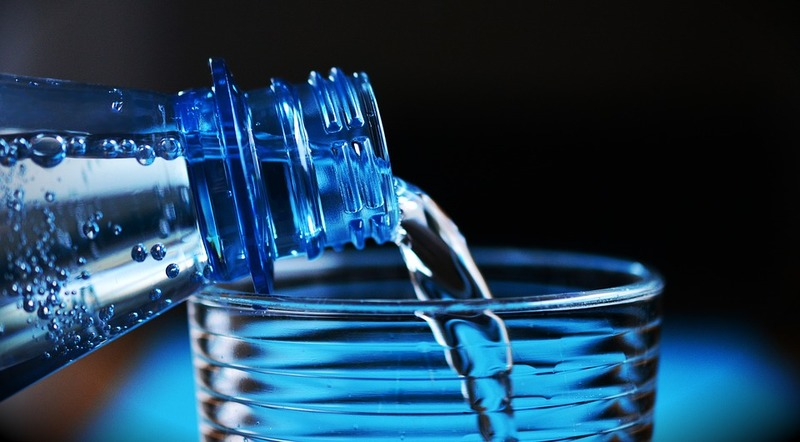 pouring water into a glass  - Benefits of Water Intake