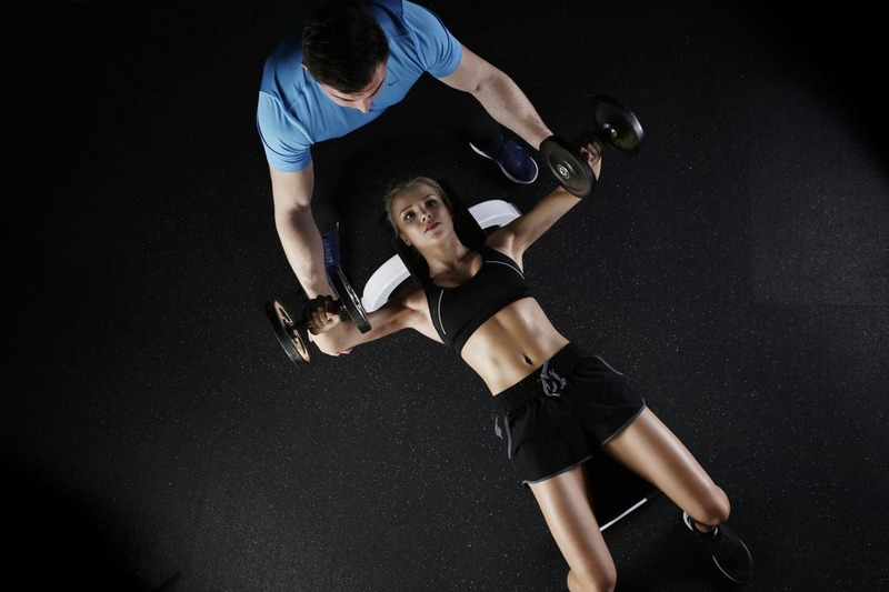 trainer and woman lifting weights  - Exercise Moves To Increase Your Metabolism