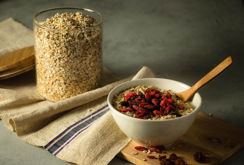 white bowl of oats, wooden spoon, container of oats