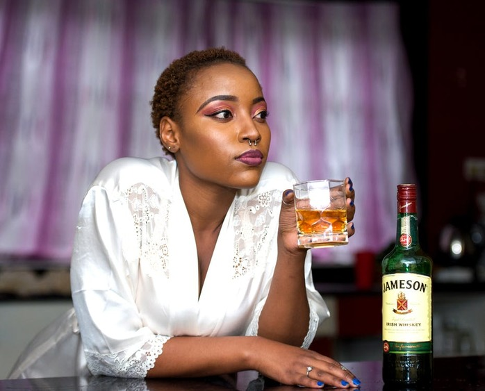 woman holding a glass of whiskey