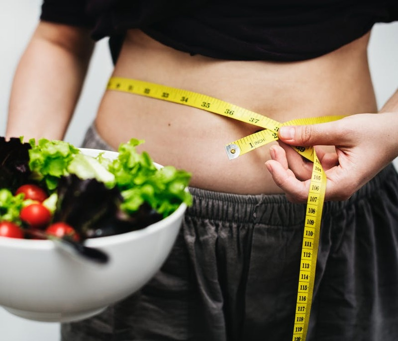 woman measuring waist line and holding a bowl of salad  - Healthy Lifestyle and Weight Loss Goals