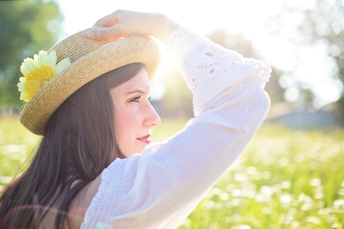 woman standing in the sunshine holding her hat
